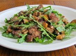 "Tender sauteed steak ""rags"" and mushrooms atop arugula dressed with a pan sauce."